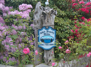 Wooden 'Welcome Sign' carved with Blue Ridge Adult Family Home, mountains, water and trees.